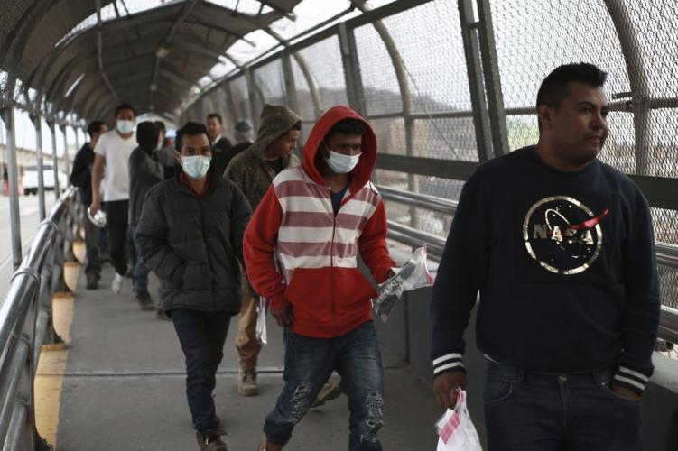 In this March 21, 2020 file photo, Central American migrants seeking asylum, some wearing protective face masks, return to Mexico via the international bridge at the U.S-Mexico border that joins Ciudad Juarez and El Paso. (AP Photo/Christian Chavez)