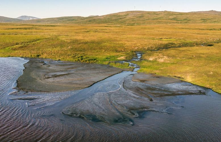A mud delta, near Nome in Northwest Alaska, was created by permafrost melting on a nearby hillside. Layers of silty soil washed into the river, changing the waterway for salmon. Image by Steve Ringman. United States, 2019.
