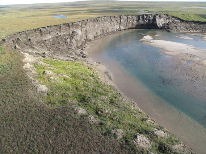 A cliff of icy permafrost is seen along the Itkillik River in northern Alaska. It is being eroded by the river. Image courtesy of Mikhail Kanevskiy. United States, 2019.