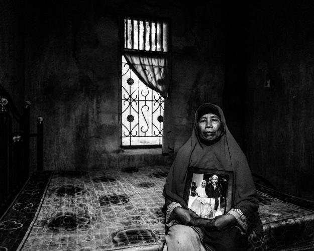 Kesuma Wati holds a photo of her and her husband, Bin Saimin, who was sent to jail for arguing with a plantation manager. Image by Xyza Cruz Bacani. Indonesia, 2018.