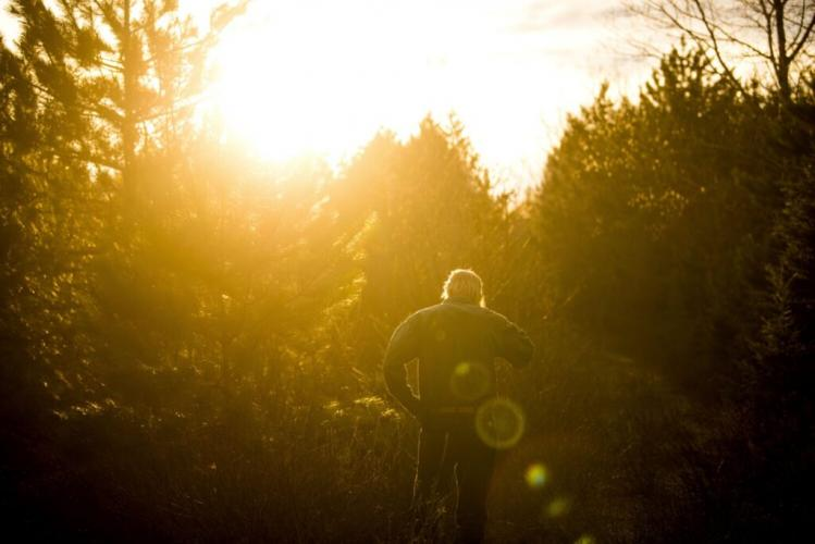 Duane Hanson walks in to the sunset near his homestead in the Unorganized Territories in the north woods of Maine near T5 R7 on May 6, 2019. Central Maine Power officials claim this area to be scarred by logging. Hanson points out that he is walking on an old logging road that has grown in. Image by Michael G. Seamans. United States, 2019.