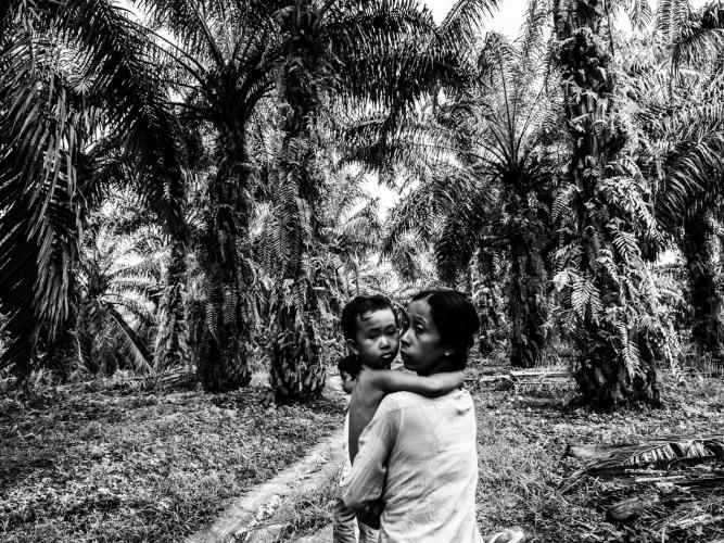 Ida and her children Santi and Fitri climb the hill home after visiting their village's only source of water, a muddy reservoir. Image by Xyza Cruz Bacani. Indonesia, 2018.