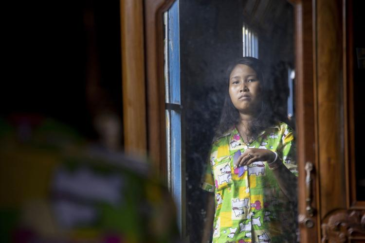 Lang Heang Khim, 22, looks in the mirror while brushing her hair in the village of Chong Trek. Image by Paula Bronstein. Cambodia, 2019.