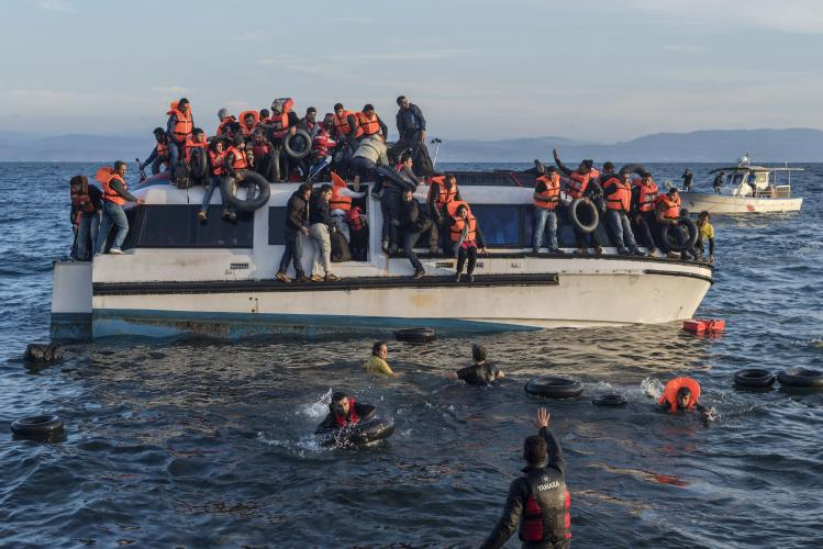 Syrian and Iraqi refugees arrive from Turkey to Skala Sykamias, Lesbos island, Greece. Spanish volunteers (life rescue team with yellow-red clothes) are from 'Proactiva open arms.' Image courtesy Ggia / Creative Commons 4.0.