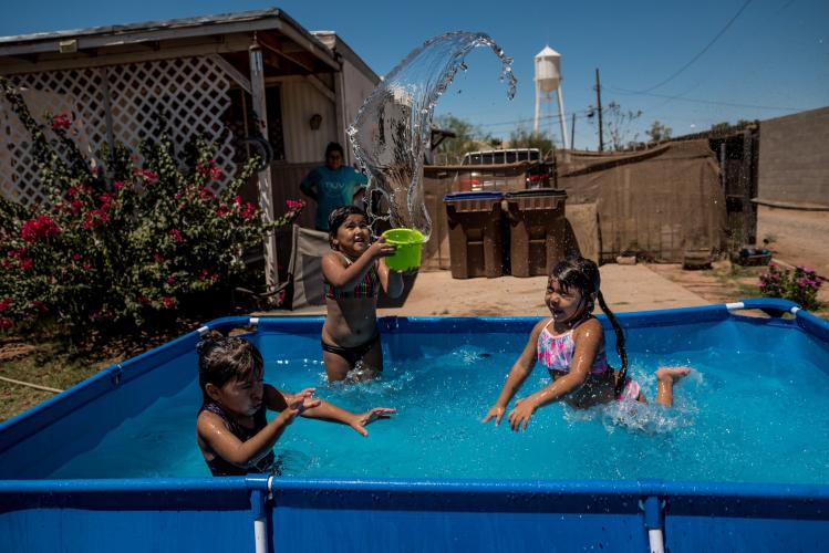 COOLIDGE, ARIZ. Marisela Felix set up a pool to keep her daughters and niece cool during 108-degree heat. Image by Meridith Kohut. United States, 2020.