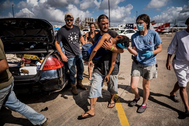 LAKE CHARLES, LA. A woman lost consciousness in a parking lot after Hurricane Laura left her without electricity or air-conditioning for several days. Image by Meridith Kohut. United States, 2020.