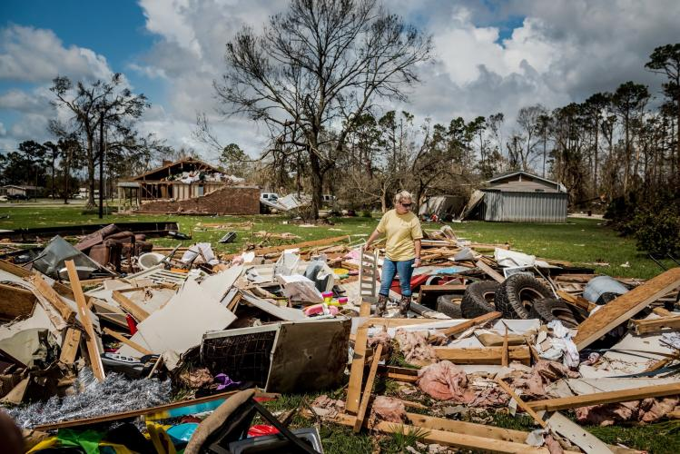 LAKE CHARLES, LA. Cassidy Plaisance surveying what was left of her friend's home after Hurricane Laura. Image by Meridith Kohut. United States, 2020.