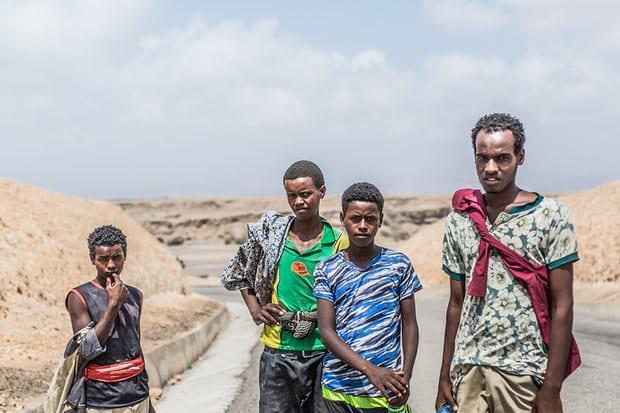 Four young migrants, from the Ethiopian region of Oromia, pictured a few kilometres north of Tadjoura en route to Obock, their final coastal destination. Image by Charlie Rosser. Djibouti, 2018.