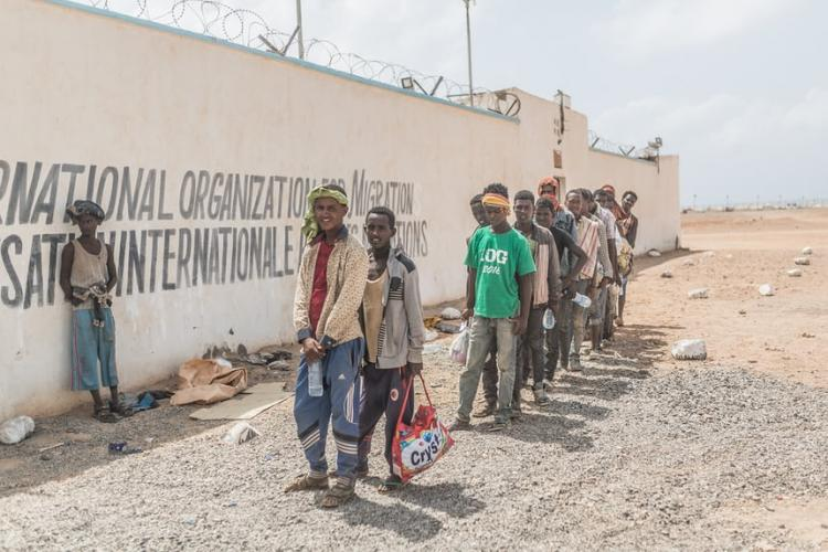 People queue to register at the IOM transit centre in Obock, where voluntary returns to Ethiopia are organised. Image by Charlie Rosser. Djibouti, 2018.