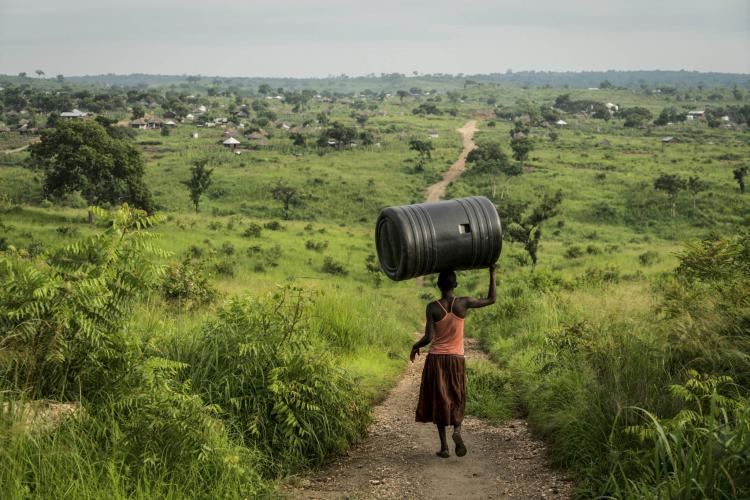 A woman carries a water tank through the Omugo settlement for refugees that have fled from South Sudan to Uganda. Uganda is the largest refugee hosting country in Africa, supporting 1.2-million people.