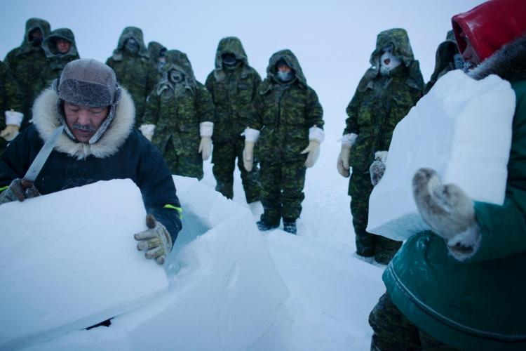 In the frigid temperatures of the High Arctic, survival means finding shelter—or making your own. Here, at a survival course held at the Crystal City training facility on Resolute Bay on the Northwest Passage, Inuit instructors Jolie Qaunaq (left) and Andy Issigaitok teach soldiers and pilots from Canada, the United Kingdom, and France how to build an iglu from blocks of snow. Image by Louie Palu. Canada, 2018.
