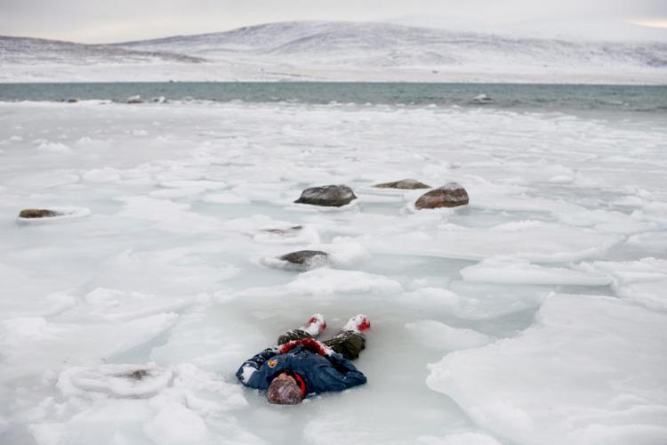 Waiting for help during a search-and-rescue training exercise, a Canadian Ranger lies in a pool of melted ice near the Clyde River community on Baffin Island. The Rangers are a volunteer reserve group mostly from Native communities across northern and remote regions in Canada. Image by Louie Palu. Canada, 2018.