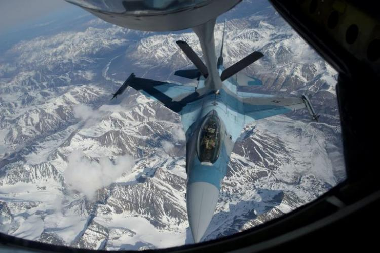 A U.S. Air Force F-16 refuels over Alaska. The fighter is part of the 18th Aggressor Squadron, a unit that plays the role of an attacking enemy—often Russian—during combat training exercises. Image by Louie Palu. United States, 2018.