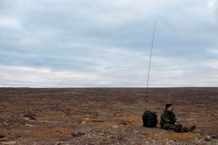 "A soldier waits by his radio on the tundra near Blue Fox Harbor on Banks Island in the Canadian Arctic. The soldier was part of Operation Nanook, an annual ""sovereignty operation,"" in which Canadian forces patrol the nation's northern territory. Image by Louie Palu. Canada, 2018."