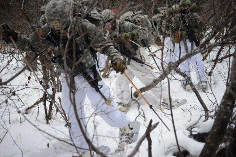 "Thick brush, deep snow, and unfamiliar gear, including snowshoes and bulky ""Mickey Mouse"" boots—so called because they resemble the feet of the famous Disney character—conspire against U.S. soldiers training for Arctic battles at the Northern Warfare Training Center. Image by Louie Palu. United States, 2018."