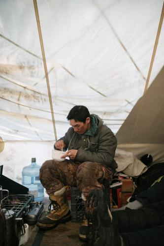 JR Nungasak scrapes a bowl clean inside a whaling camp tent as he takes a break from the perpetual watch of whaling. Image by Kiliii Yuyan. United States, undated.