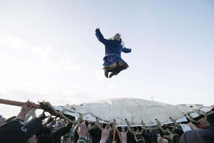 In a festival tradition that goes back millennia, Inupiat villagers join together to toss successful whalers into the air to celebrate a successful whaling season and to give thanks to the whale for its gift. Image by Kiliii Yuyan. United States, undated.