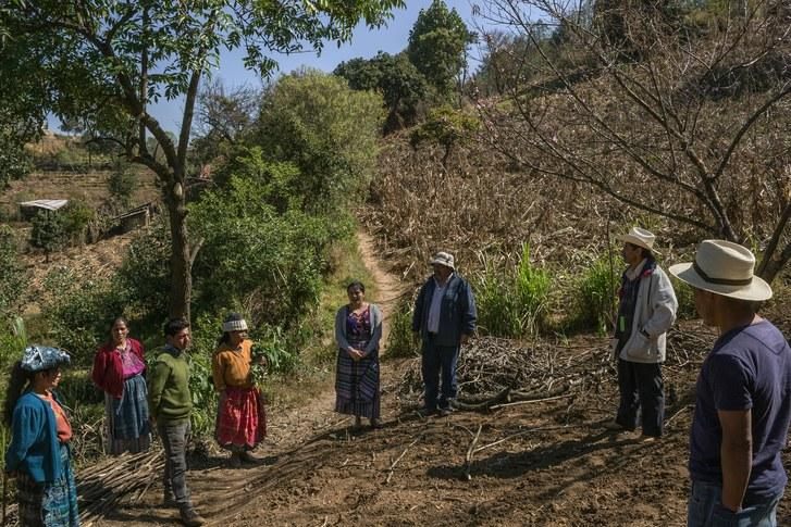 Sebastian Charchalac talks to villagers in a field in Paraje León. Trained agronomists, through grants, have been instructing rural communities in diversifying crops, conserving water, and reforesting some of the surrounding areas. Image by Mauricio Lima. Guatemala, 2019.
