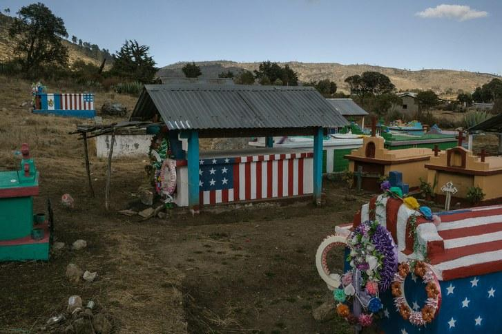 Graves painted with the U.S. flag, in the cemetery of Todos Santos Cuchumatán, indicate that the deceased died as immigrants in the U.S. The families paint the flags as a symbol of thanks for money that their loved ones sent home from the U.S. Image by Mauricio Lima. Guatemala, 2019.
