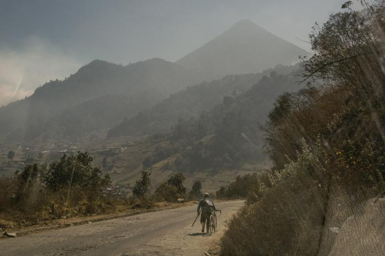 A villager walks along a road down the Siete Orejas mountain, outside the village of Xecaracoj, with the Santa María volcano in the background. Image by Mauricio Lima. Guatemala, 2019.