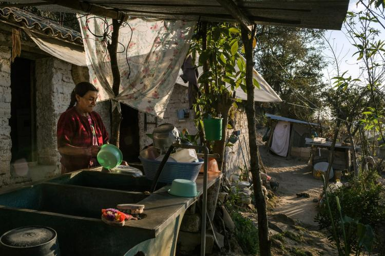 Clara Luz Lucas washes dishes outside her home, in the western highlands. Lucas has a daughter living in Houston. Image by Mauricio Lima. Guatemala, 2019.