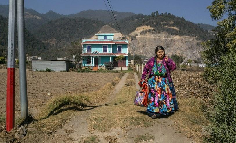 A Maya woman outside her home, which was funded by remittances from a relative living in the United States. Image by Mauricio Lima. Guatemala, 2019.<br />