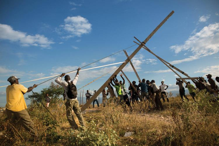Residents of Canaan raise the first of three handmade utility poles, part of an improvised effort to receive electricity from the state power grid. Image by Allison Shelley. Haiti, 2017.<br />
