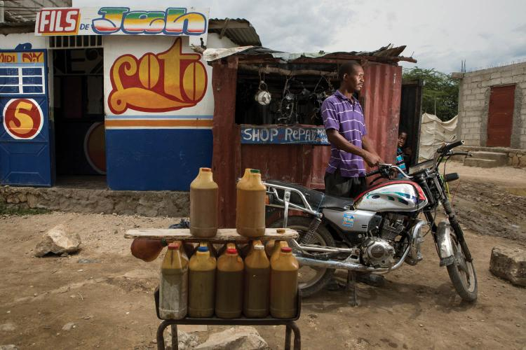Jacob Viknel at his motorcycle-repair shop in the Jerusalem section of Canaan. When customers pull up, Viknel fills their tanks with gasoline from the jugs on display. Image by Allison Shelley. Haiti, 2017.