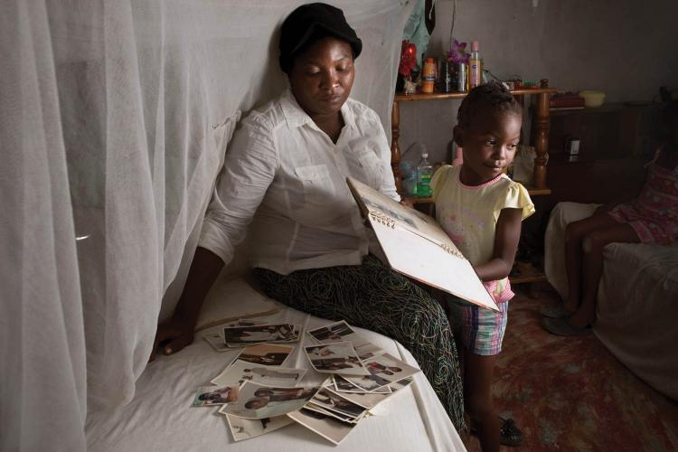 Magalie Gabriel, the widow of Smith Merzeus, with their daughter, Rachel. Merzeus was assassinated in a drive-by shooting outside their home in Canaan 5. Image by Allison Shelley. Haiti, 2017.<br />