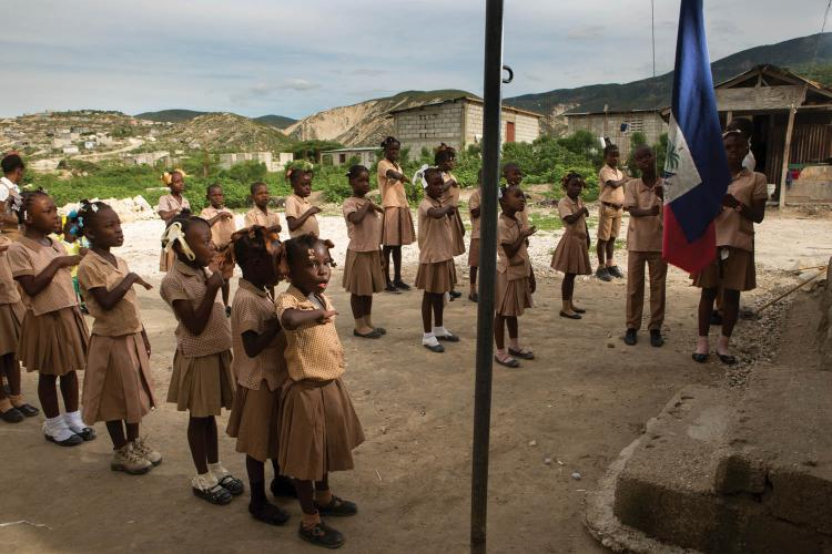 Children sing the national anthem as the Haitian flag is raised at their elementary school, which doubles as the Church of the Nazarene, in the Onaville neighborhood. Pastor Marc Loumette founded the church and school in 2010, after his calling to minster to those affected by the earthquake. Image by Allison Shelley. Haiti, 2017.