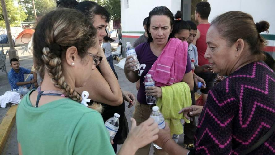 A Mexican volunteer, right, gives water to Cuban migrant women living in a makeshift camp by the Gateway International Bridge in Matamoros, Mexico. Image by Jose A. Iglesias. Mexico, 2019.