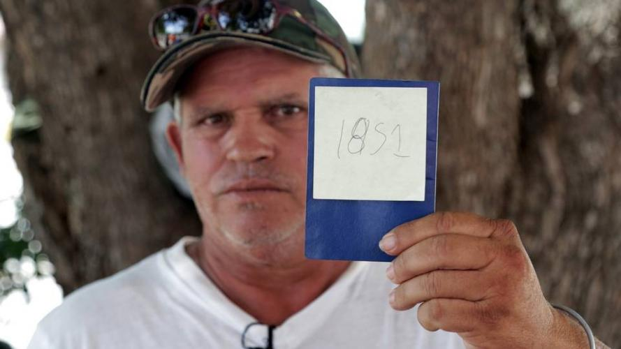 Jorge Luis Fleites, a Cuban migrant currently waiting in Matamoros, Mexico, for his chance to ask for asylum in the United States, holds up his number in line. He has been waiting for two months since he arrived at the border and was hoping to be able to get in in the next few days after this photo was taken. Image by Jose A. Iglesias. Mexico, 2019.