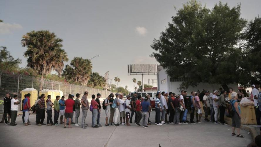 Migrants line up for food at a camp located on the Matamoros, Mexico, side of the Gateway International Bridge that connects Matamoros to Brownsville, Texas. Church and volunteer organizations in Brownsville provide water and food for the migrants on the Mexican side of the border as they wait for their asylum requests to be processed. Image by Jose A. Iglesias. Mexico, 2019.