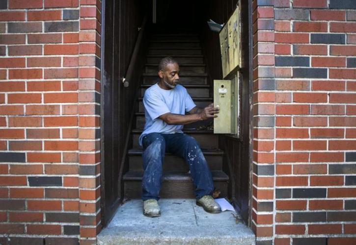 Charles Roberts fixes a mailbox for an apartment he is doing maintenance on to prepare for tenants to move into at the Reserve at Heritage Apartments in the Ville on Tuesday, Dec. 22, 2020. Roberts has been doing maintenance work for about 30 years and previously helped maintain the Preservation Square apartments in the Carr Square neighborhood. He used to work with Valerie Nichols who worked and lived in the apartments at Preservation Square and made the living conditions of the members of her community there a priority. Photo by Cheyenne Boone. United States, 2020.