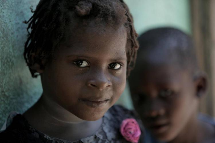 Marie Stacey (left), 6, and her friend Lukenson, 4, are curious about visitors to their town, Bellanger in Haiti's Artibonite Valley. The girl's mother, Paula Paul, has advanced cervical cancer. Image by José A. Iglesias. Haiti, 2018.