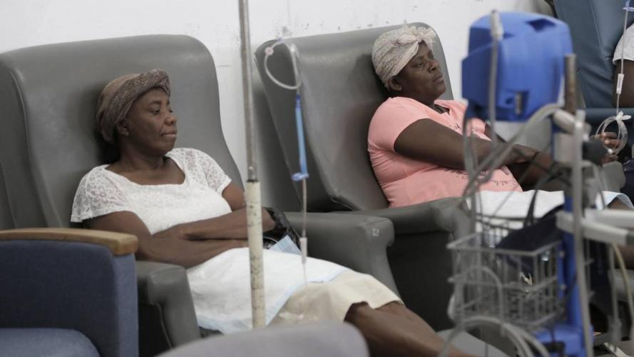 Paula Paul, right, and Feonia Licin patiently await the start of their chemotherapy at the University Hospital of Mirebalais in central Haiti. Paul has cervical cancer and Licin, breast cancer. Image by José A. Iglesias. Haiti, 2018.