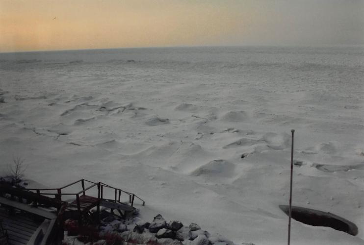 This is a photo of the ice shelf extending out from the beach at Nancy Schwab's vacation home in the early 1990s. As the Earth warms, that ice shelf is not there to protect the beaches and dunes along Lake Michigan from erosion. Courtesy of Nancy Schwab.