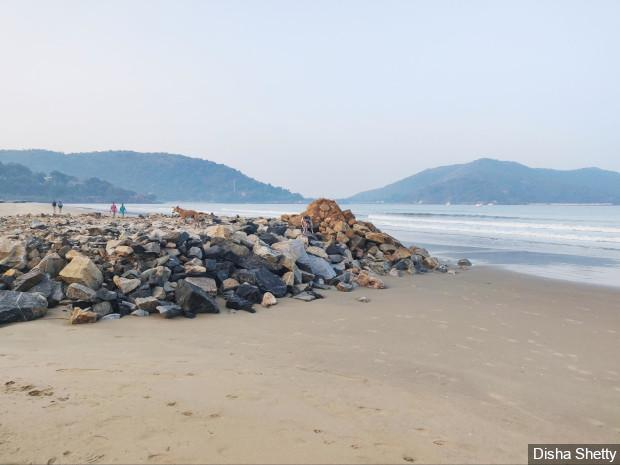 Breakwaters, part of Karwar port expansion work, have been constructed by dumping rocks on the beach. Experts point to the futility of building such structures here because Karwar is a sheltered beach, meaning the wave speed is already reduced by its surrounding islands. Image by Disha Shetty / IndiaSpend. India, 2020.