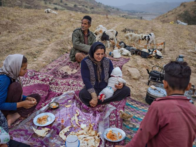 Stopping for the night, the Zamani family shares a meal laid out on colorful rugs. Image by Newsha Tavakolian. Iran, 2018.