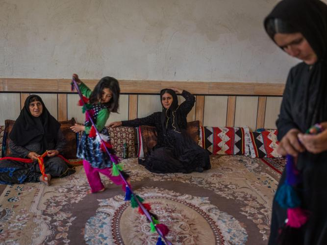 Bibi Jan Mokhtari (center), 57, and Mahpasand Mokhtari (left), 62, are living in a house for the first time. Elham Mokhtari, six, plays with a handicraft made by her mother, Mahnaz Mokhtari (far right), 39. The family makes and sells handicrafts as a main source of income. Image by Newsha Tavakolian. Iran, 2018.