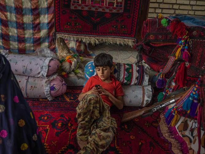 Mostafa Mokhtari, 10, sits in a tent in his grandparents' yard. His grandparents decided to stay in a house to help their grandchildren attend school and study. But being accustomed to living in a tent, they made one for the yard. Image by Newsha Tavakolian. Iran, 2018.