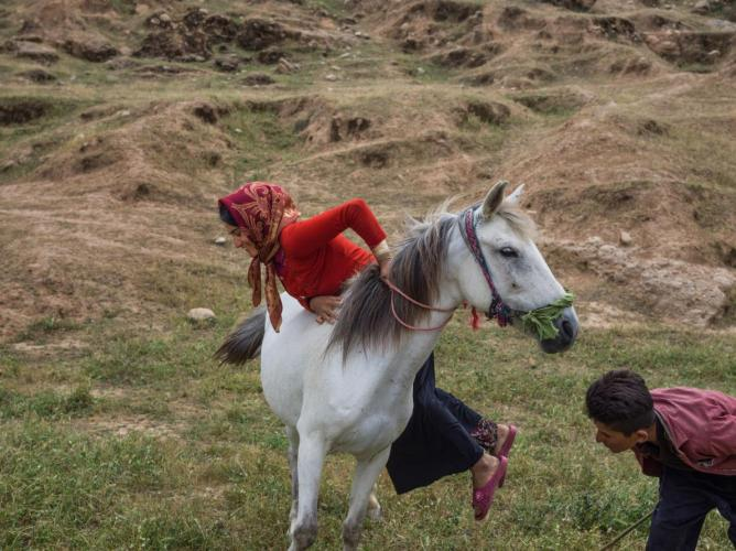 Parisa Zamani, 20, climbs onto her horse. She is considered an accomplished rider in her family. Many nomadic families have changed their lifestyles and settled in cities so girls may go to school. Image by Newsha Tavakolian. Iran, 2018.
