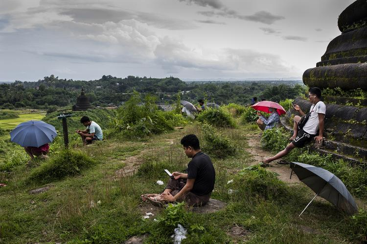 People sit on a hill to search for a 3G signal in Mrauk U, Myanmar, on Aug. 20. The government has blocked high-speed internet in the township since June 2019. Image by Hkun Lat/Foreign Policy. Myanmar, 2020.