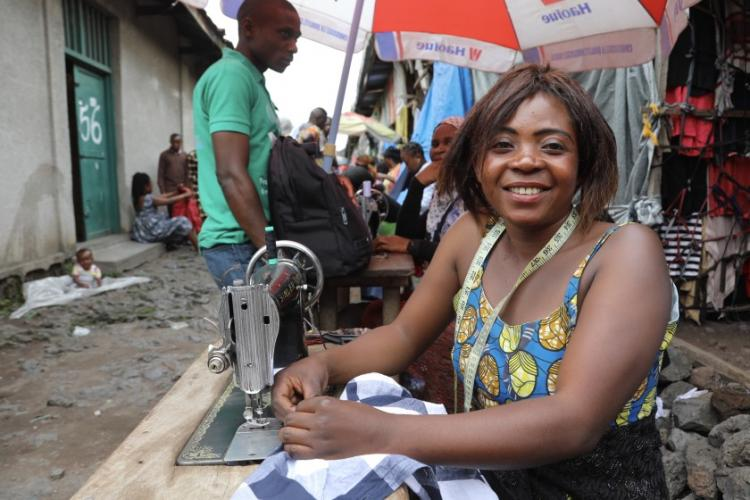 "Kajang Anuaritte, a 27-year-old tailor and mother of five children, works out of Virunga market in Goma, Congo. ""There's hundreds of us here packed together, it will spread easily,"" she said of the coronavirus. Image by Peter Yeung / LA Times. Congo, 2020."