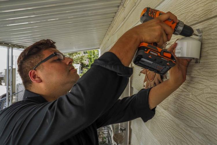Yanni Gonzalez, a public outreach and community coordinator for the Central California Asthma Collaborative, installs an air quality monitor at the home of Kira Hinslea. Image by Larry C. Price. California, 2018.