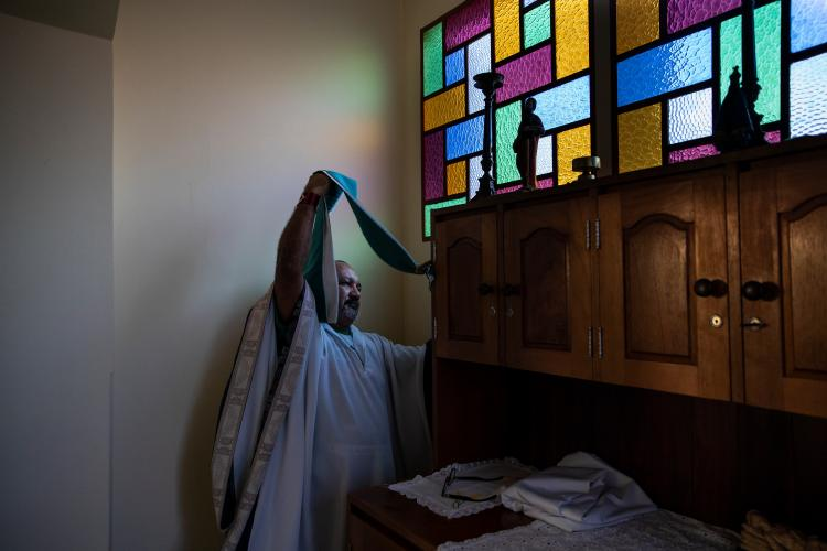 Father Amaro Lopes prepares to celebrate a mass in a chapel at the bishop's house in Altamira. Image by Spenser Heaps. Brazil, 2019.