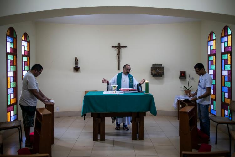Father Amaro Lopes, center, celebrates a mass in a chapel at the bishop's house in Altamira. Image by Spenser Heaps. Brazil, 2019.