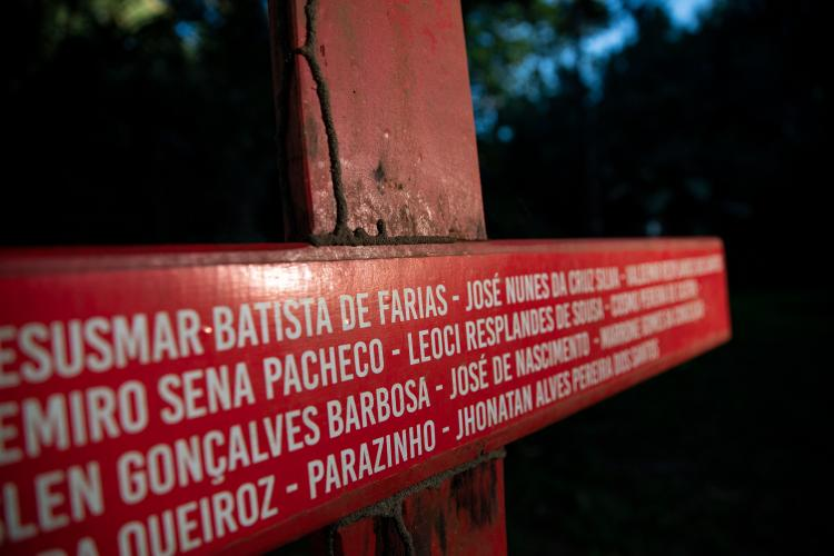 A cross bearing the names of people killed over land conflicts in Anapu stands beside the grave of Sister Dorothy Stang in the Brazilian town. Image by Spenser Heaps. Brazil, 2019.