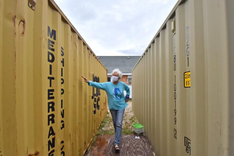 Mickey Baker, co-owner of Mermaid's Folly, moves between two storage containers holding the contents of her shop on Ocracoke Island. Image by Dylan Ray. United States, undated.
