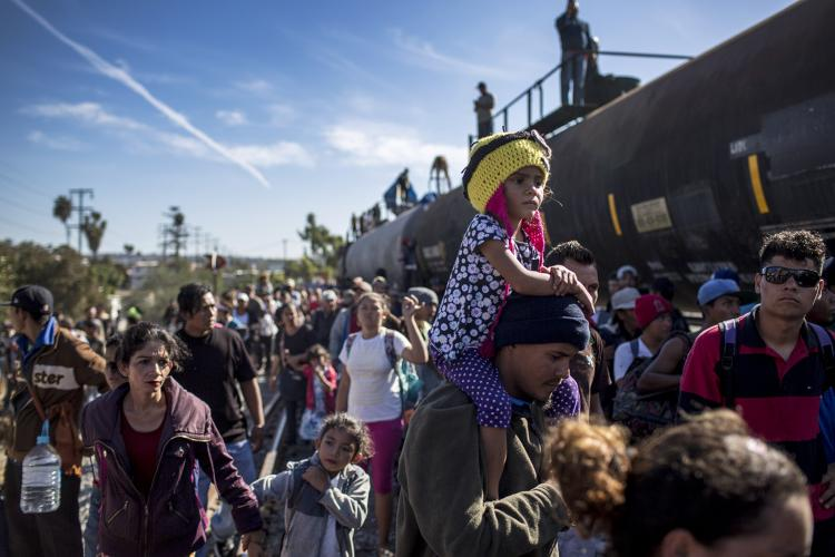 Hundreds of Hondurans move towards the border wall, coasting the wagons of the trains parked near the vehicle port of Chaparral. Image by Simone Dalmasso. Tijuana, 2018.